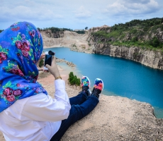 A girl taking shot of her new shoes with the newly discovered blue lake as the background.