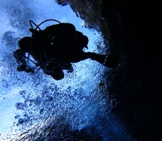 Silfra Fissure.  A tear in the earth's crust where tectonic plates meet.  Man diving in glacial waters between two continents.