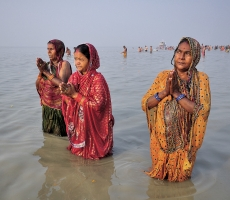 Devotees praying to The Sun after having a dip at The Annual Ganga Sagar Fair.