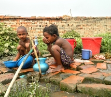 two children in brick field using tap water.