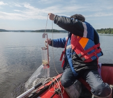 On a picture the hydrologist researches the parameters of fresh water on the  lake in Karelia.