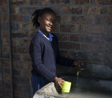 A school girl drinking fresh water in a small village, Guguletu in South Africa.