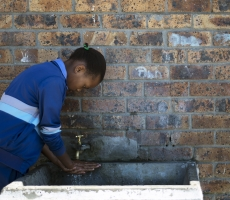 A school girl washing her hands with fresh water in a small village, Guguletu in South Africa.
