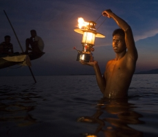 A night fisherman who catches fishes in the water by lamp