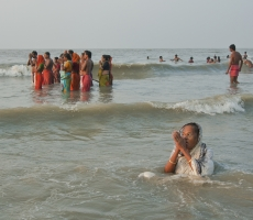 the devotee is praying to the sun-god on the occasion of pious-moment, sitting on the submerged sand of the sea, at Gangasagar, another natural resource.